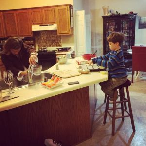 Amber and the boy child make cupcakes.
