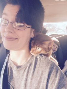 Cat on shoulder, child in backseat